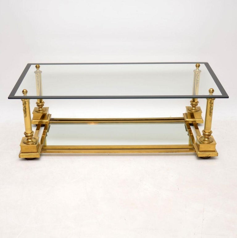 A stunning and very well made coffee table by Maison Charles, this was made in France around the 1950s-1960s. It has a beautiful brass frame, with a thick glass top and mirrored glass lower tier. The condition is very good throughout, with only some