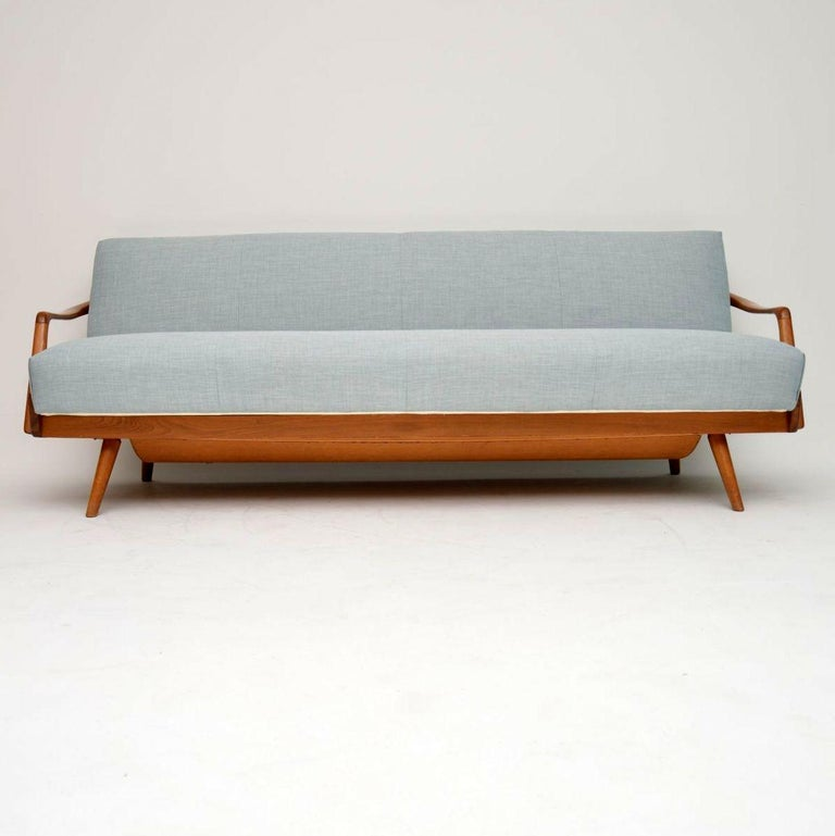 A stunning vintage sofa bed, this was made in France and dates from circa 1950s-1960s. We have had it fully re-upholstered in our lovely light blue fabric. The solid wood frame is a light wood that looks like it could be Ash, it's clean, sturdy and