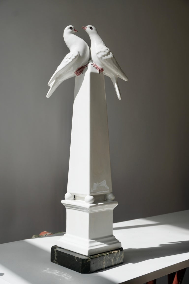 A gorgeous porcelain obelisk on a marble base. The lovely white color porcelain obelisk with highly crated white, hand painted love birds on the top.  Great condition. Italy 1950s. Measures: Height 55 cm , width 15 cm, depth 15 cm. Weight 2