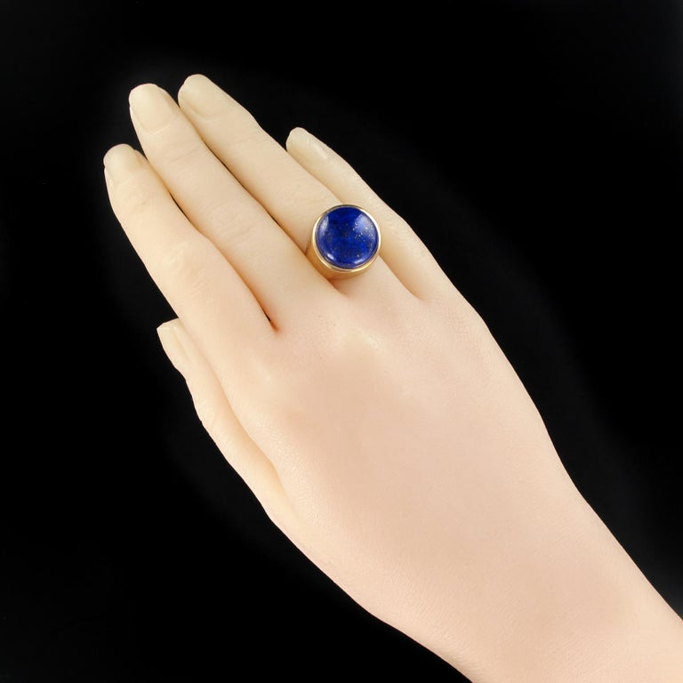 Ring in 18 karats yellow gold, eagle's head hallmark. Lovely signet ring, it is closed set on its top with a flat cabochon lapis lazuli. The entire frame is crafted with precision and refinement. Height: 17.1 mm, width: 17.3 mm, thickness: about 10