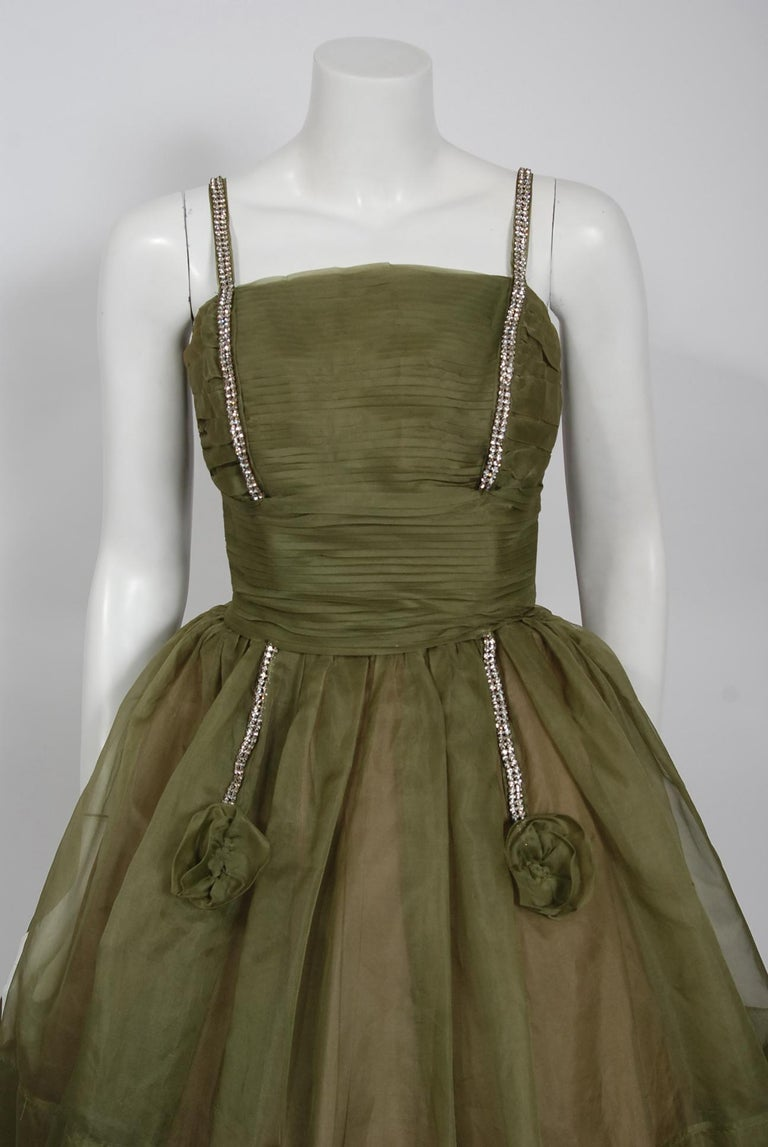 Fashioned from rich olive-green light weight silk-organza, this 1950's creation has everything a woman wants. The bodice has a gorgeous pleated texture shelf-bust design. I adore the sparkling rhinestone detail which is so playful and elegant at the