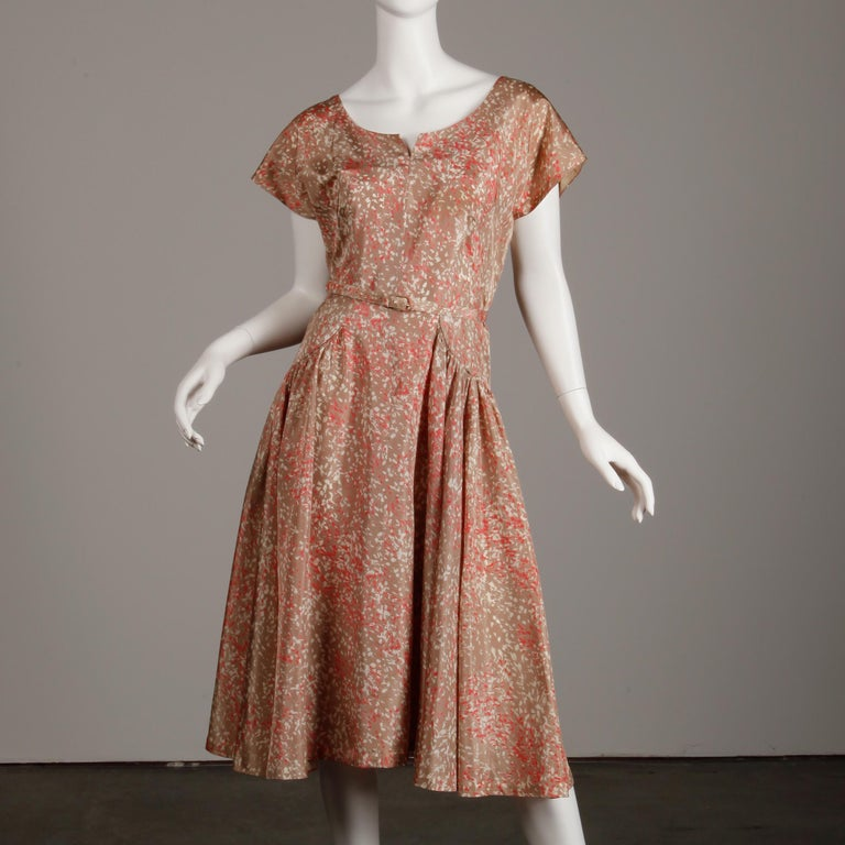 Rare 1950s size large! This vintage ensemble comes with a dress, coat and matching belt in a fantastic mid century print done in pink, beige and mauve. The dress is unlined with rear metal zip and hook closure. The dress bust measures 38