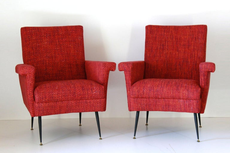 A pair of two vintage armchairs with red cover and iron and brass feet. Typical italian mid century style.  The vintage armchairs have been fully restored. The filling of the seat has been changed and the cover textile changed with a brand new
