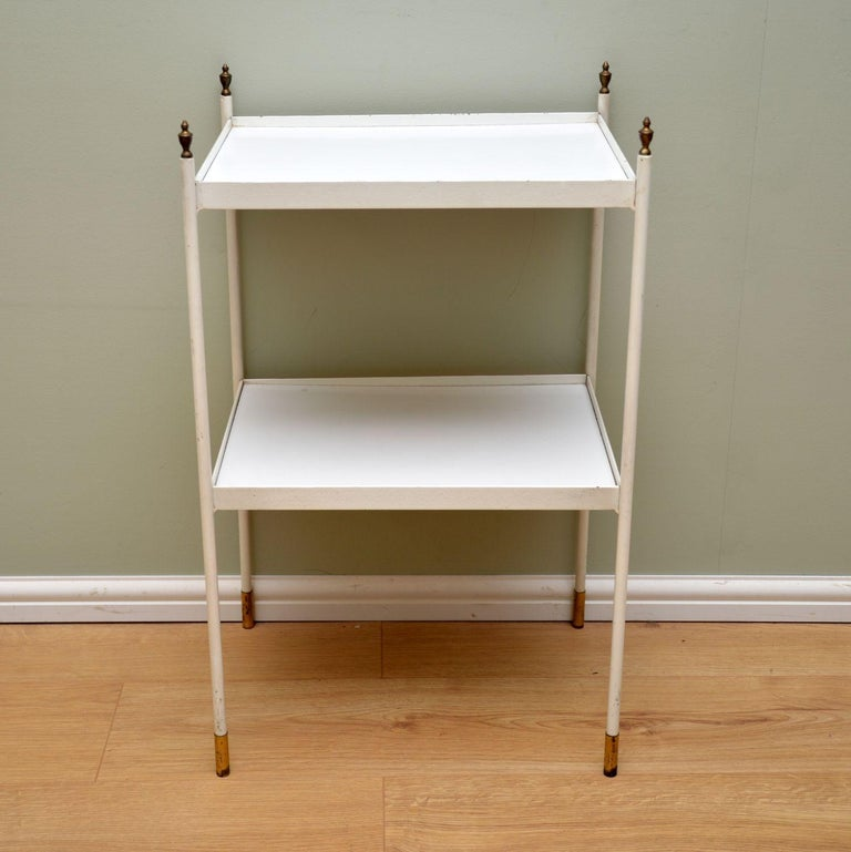 A stylish and elegant vintage two-tier side table. This dates from circa 1950s-1960s, it's of lovely quality.  This has a painted white steel frame, with brass finials and feet caps. The shelves are wood with white Formica tops.  The condition