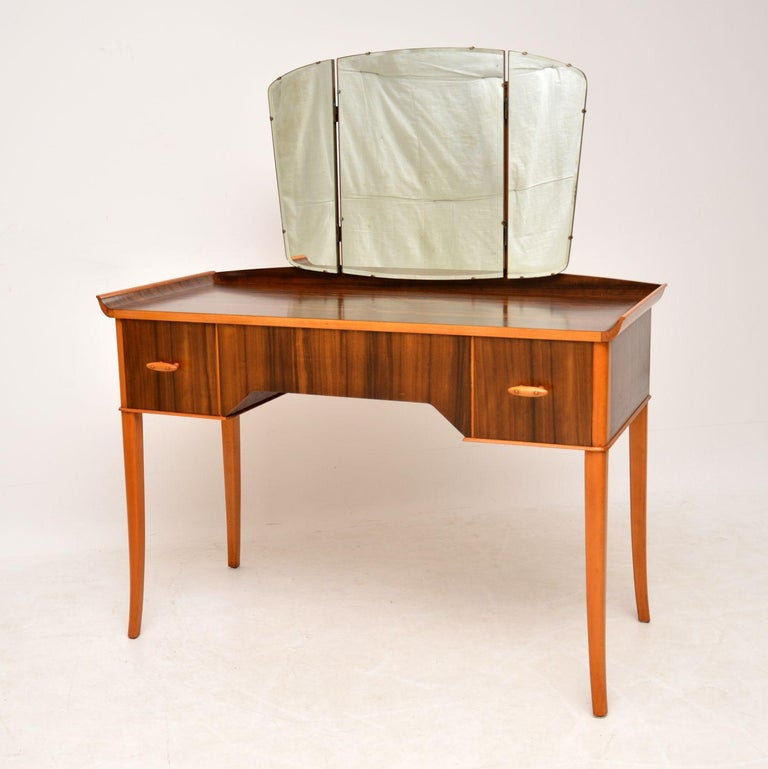 A stunning and top quality vintage dressing table, beautifully made from walnut contrasted with beech. This was made by Vesper furniture in England, it dates from the 1950-1960s. The design is lovely, with slender tapered legs and very interesting