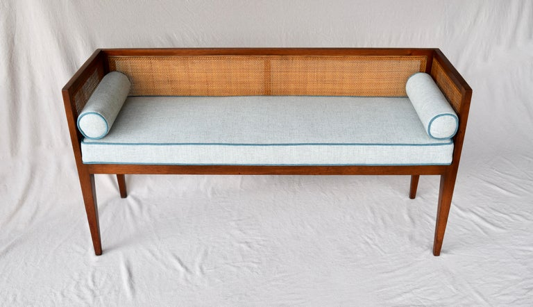 Solid walnut Mid-Century Modern window bench or settee attributed to Edward Wormley for Dunbar. Lithe line design constructed of walnut frame with original fine scale caning. Restored seat and bolster cushions are upholstered is soft blue linen