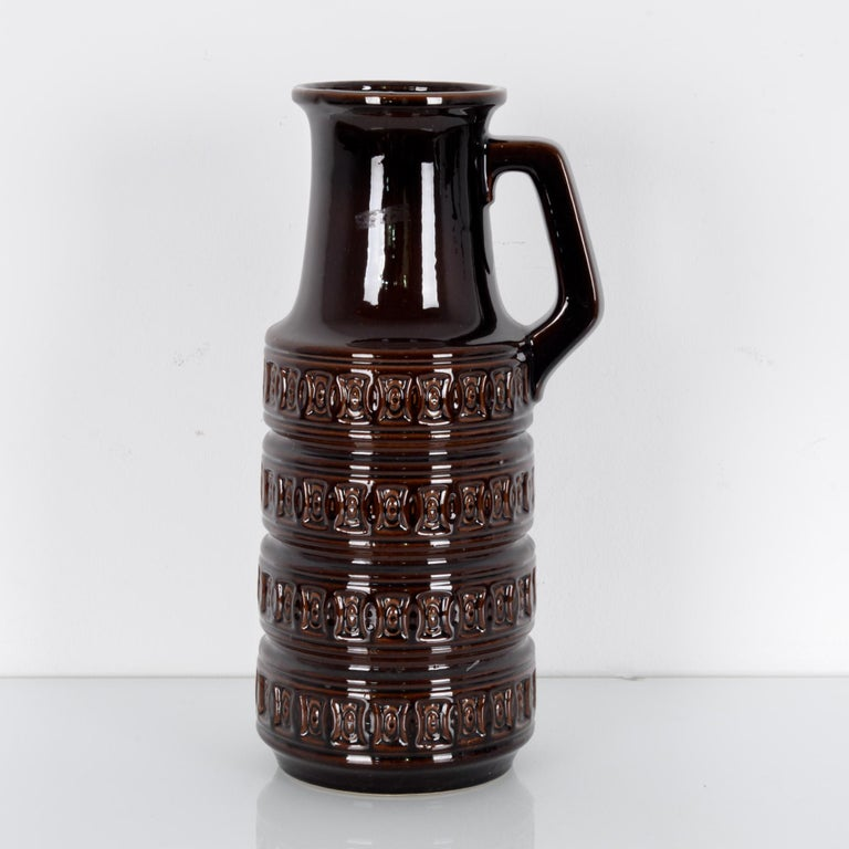 A ceramic vase produced in West Germany, circa 1950. This handled vase coated in brown glaze stands at 45 cm tall. Art pottery was a flowering movement in midcentury West Germany, here characterized by the engraved pattern, thick layer of glaze, and