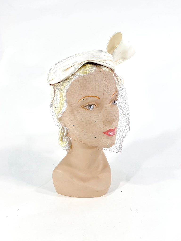 1950s White silk satin cocktail hat with an enlarged sculpted bow that finished the gathered edge at the base of the hat. The full-face veil is a soft tan color decorated with clear rhinestone accents.