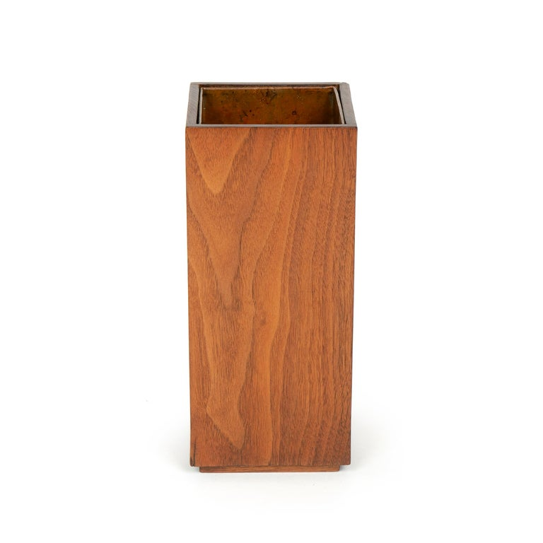 A copper lined rectilinear walnut planter / vase, on a small plinth base.