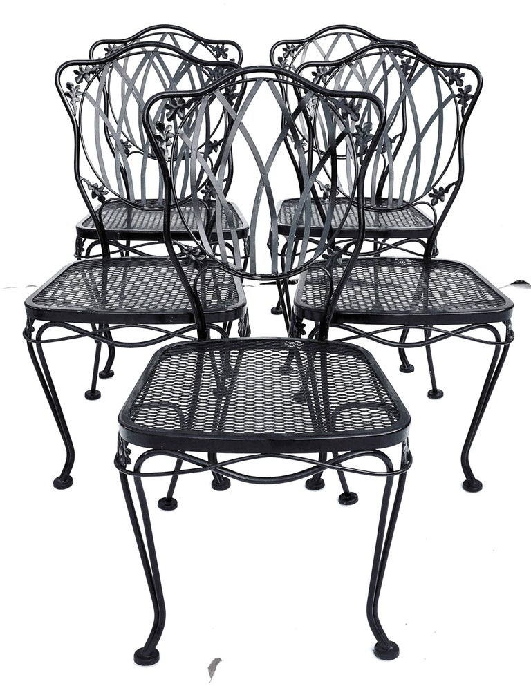 Midcentury set of five wrought iron floral and vine motif metal mesh chairs by, Russell Woodard. Features a floral and vine motif and the original black painted indoor outdoor treated finish. Includes the original and detachable seat cushions.