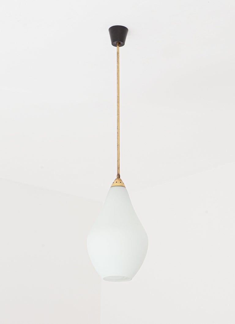 Mid-Century Modern pendant lamp manufactured in Italy during the 1950s. The ceiling light feature very light green opaline glass and brass parts  Very small crack under the glass, difficult to notice. Brass with original patina.   The style recalls