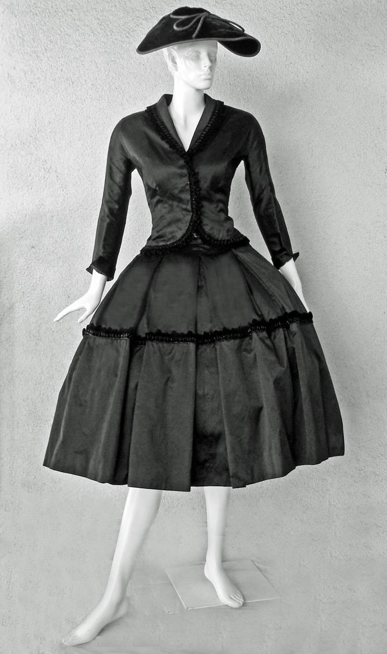 Two piece suit consisting of a jacket and mid length skirt of butter black satin trimmed with a velvet and jet fringe. The fitted jacket is constructed on princess lines with raglan sleeves, a cutaway closure and small peplum. The full ballerina