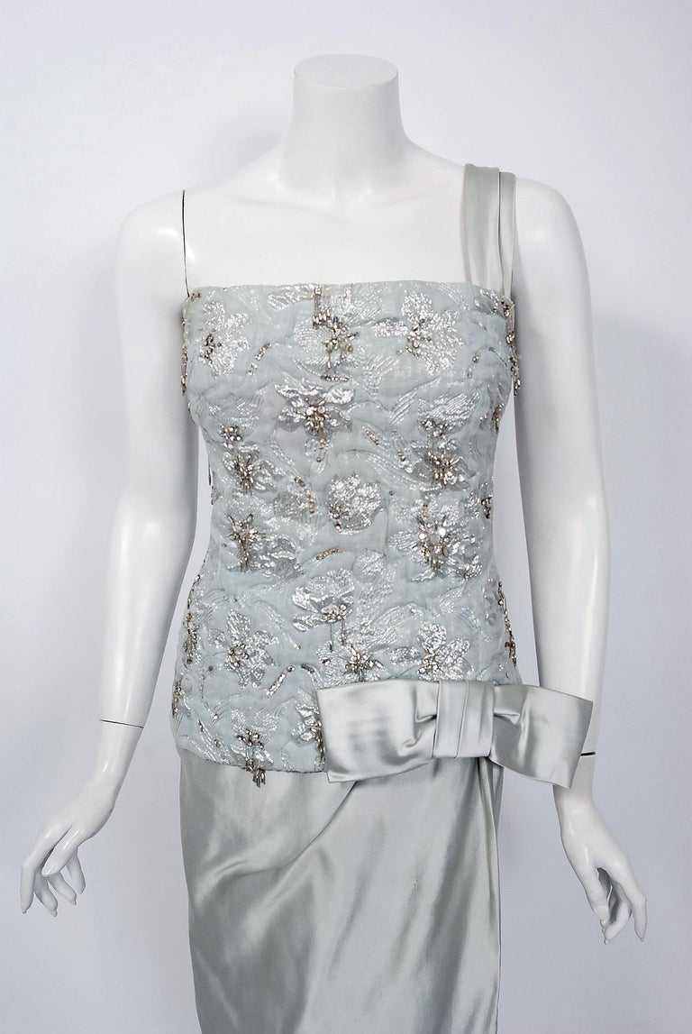 Beautiful ice-blue beaded metallic silk and satin gown by the famous House of Maggy Rouff. This gorgeous garment dates back to their 1955 haute couture collection. Harmony and simplicity were cornerstones of Maggy Rouff's belief in elegance as a way