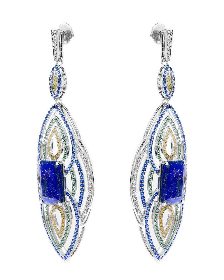 Blue, yellow, white and green sapphires are pave set around this pair of 18k gold and lapis earrings. Inspired by ancient Egypt, the centre stone of lapis weighing a total of 19.56 carats bring a Khemetic mystique to your profile.
