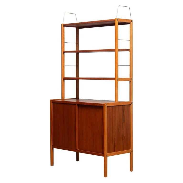 Beautiful and elegant teak bookcase cabinet with brass details by Bertil Fridhagen for Bodafors, Sweden, 1960s.  The lower part of the cabinet has two sliding doors and inside the original shelf with logo