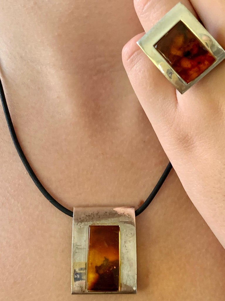This 1960-1980's era three piece set features beautiful Amber in a pendant, ring and earrings.  The silver is marked 925.  The necklace cord is 18
