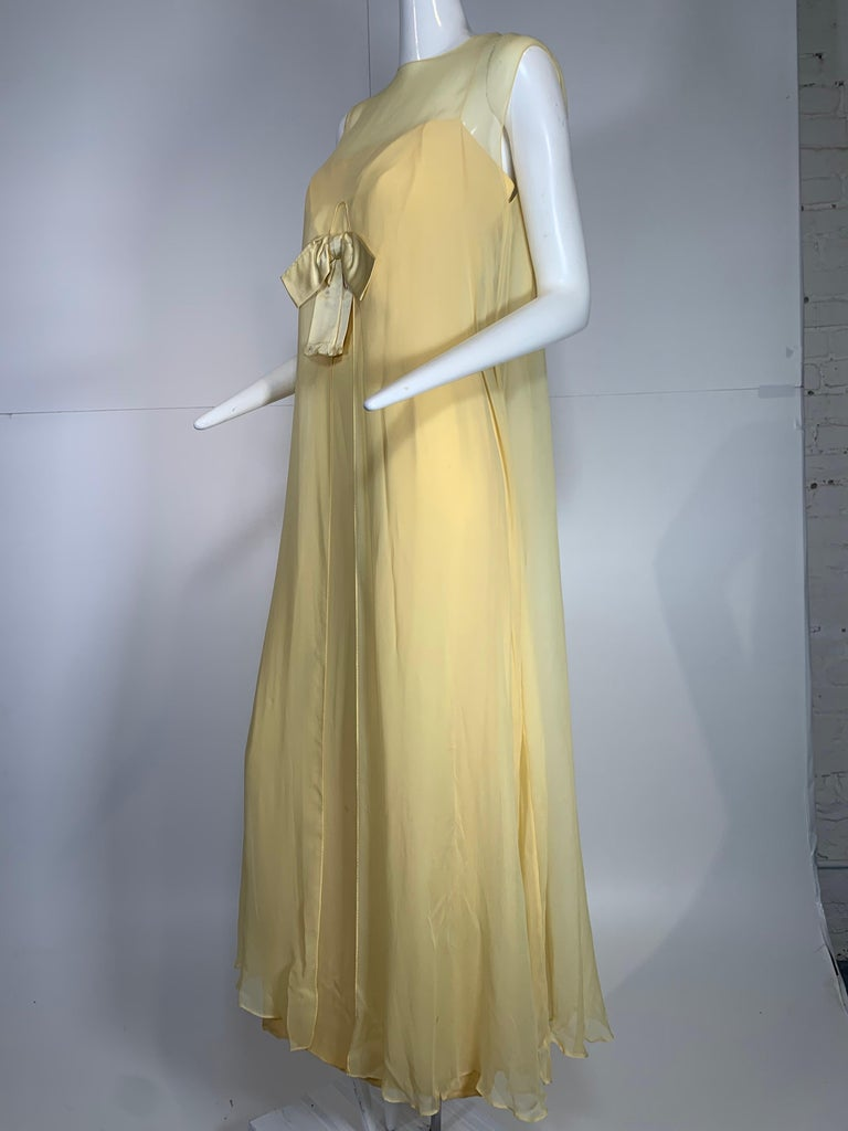 1960s Bonwit Teller pale butter yellow silk chiffon column gown with front bow. Separate overlay layer which is split at front allowing the bow on gown bodice to sit outside the overlay. Zipper at back of column. So gorgeous.