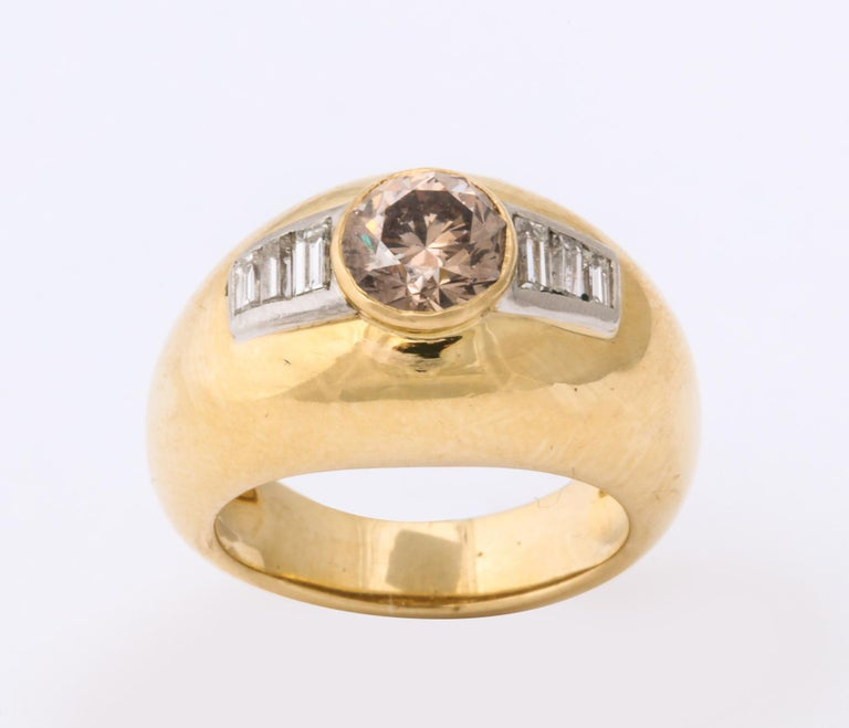 One Unisex Ring 18kt High Polish Yellow Gold Ring Designed With A Natural Fancy Colored Light Brown With Pinkish Tinge 1.10 Ct  Diamond. Ring Is Further Flanked With Six Baguette Cut Diamonds Weighing Approximately .40 Cts Total Weight. All Baguette