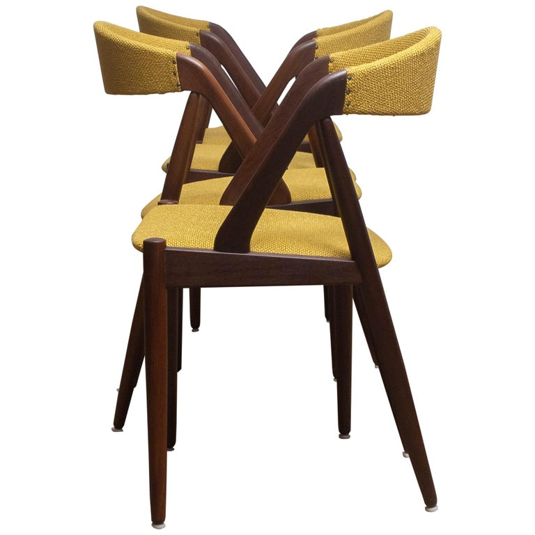 A beautiful set of four dining chairs by Kai Kristiansen for Shou-Andersen Møbelfabrik. The chairs are made of walnut frames with new ochre / gold color upholstery. They are in a wonderful condition. Period: 1960s.