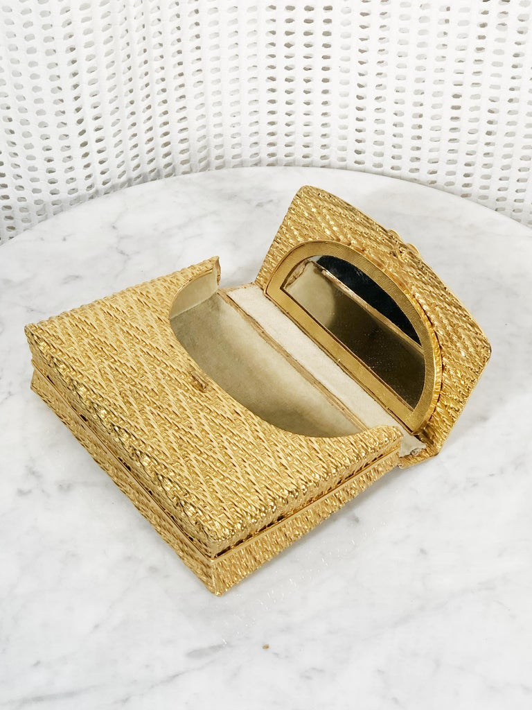 A gorgeous 1960s Italian gold metal basket weave evening box clutch with hinged lid, velvet lining and a fixed mirror on lid. Height is 5 inches, width is 6 inches. Condition very good. Slight wear on back and on clasp. One tiny stone discolored.