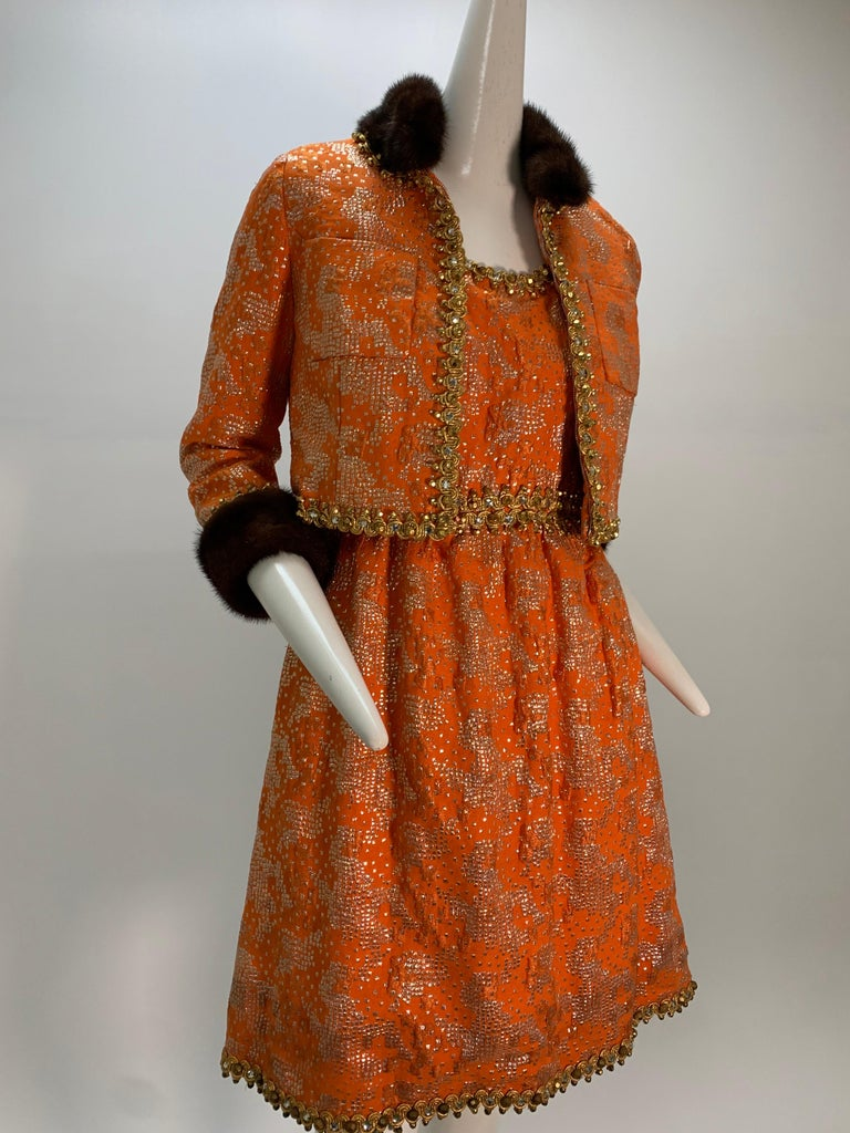 1960s Oscar De La Renta tangerine silk lame brocade cocktail dress and jacket ensemble: orange silk with silver lame square patterns scattered throughout a tank-style dress trimmed with gold braidwork at waist, and neckline and hem. The waist length