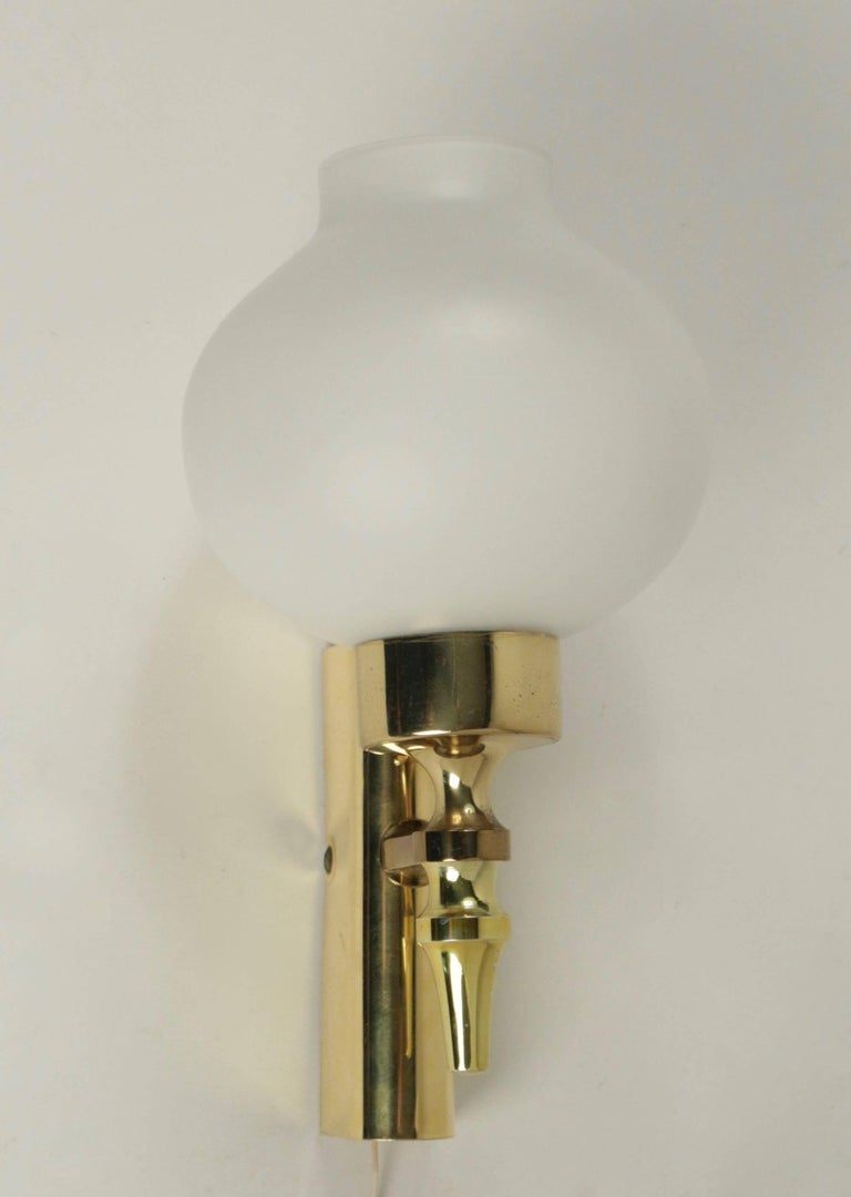 Composed of a wall support formed by a half cylinder positioned in height in gilded brass. From the wall base leaves a stem on the low part which support the arm of light dressed with a white satin opaline of origin put on a round cylindrical base