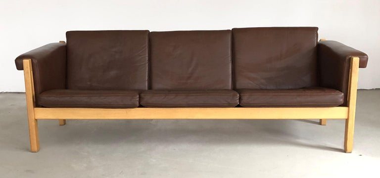 Three-seat Danish sofa in oak by Hans J. Wegner for GETAMA   The rarely seen model GE-40 sofa with it´s simple but elegant Wegner design feature a strong oak frame with small and simple yet elegant details and original brown leather cushions, has