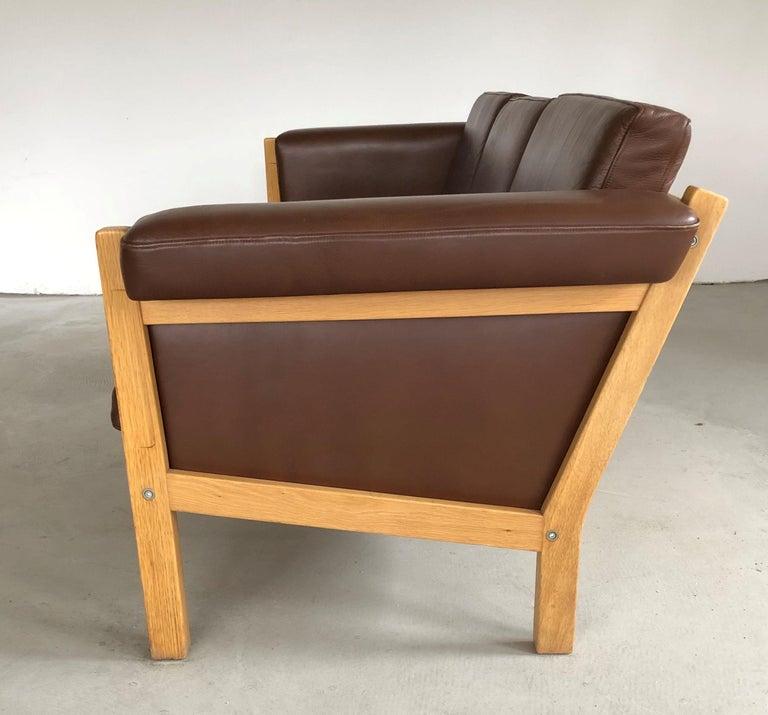 Adam Style 1960s Danish Hans J. Wegner Three-Seat Sofa in Oak and Brown Leather by GETAMA For Sale