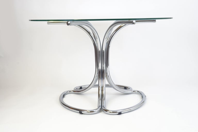 An Italian dining table of the late 1960s. Its tubular steel construction is stylized into a leaf shape, providing poetry and lightness to this object. Finally, the glass top enhances the appearance in a positive and transparent way.