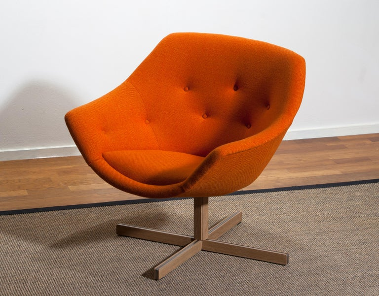 Fantastic 'Mandarini' swivel armchair made by Carl Gustaf Hiort for Puunveisto Oy, wood work Ltd. This chair is upholstered with a buttoned orange fabric 'Hallingdal' by Kvadrat designed by Nanna Ditzel on an oak swivel base. It is in perfect and