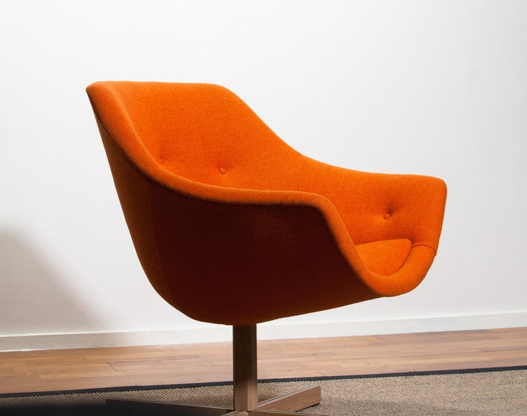 Fantastic 'Mandarini' swivel armchair made by Carl Gustaf Hiort for Puunveisto Oy, wood work Ltd. This chair is upholstered with a buttoned orange fabric 'Hallingdal' by Kvadrat designed by Nanna Ditzel on an oak swivel base.