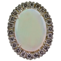 1960s 18 Karat Gold Oval Opal with a Halo of Round Diamonds Ring