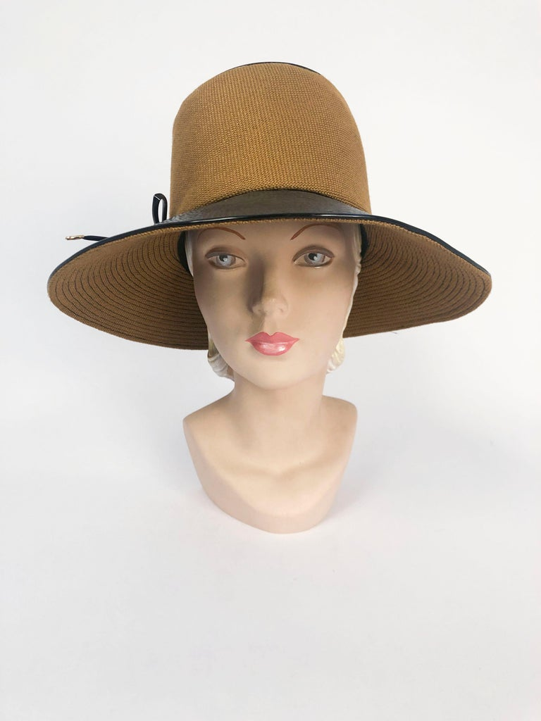 1960's/1960's Black and Khaki Vinyl Wide Brimmed Hat with tall crown, matching black rolled piping, and bow tipped with brass accents