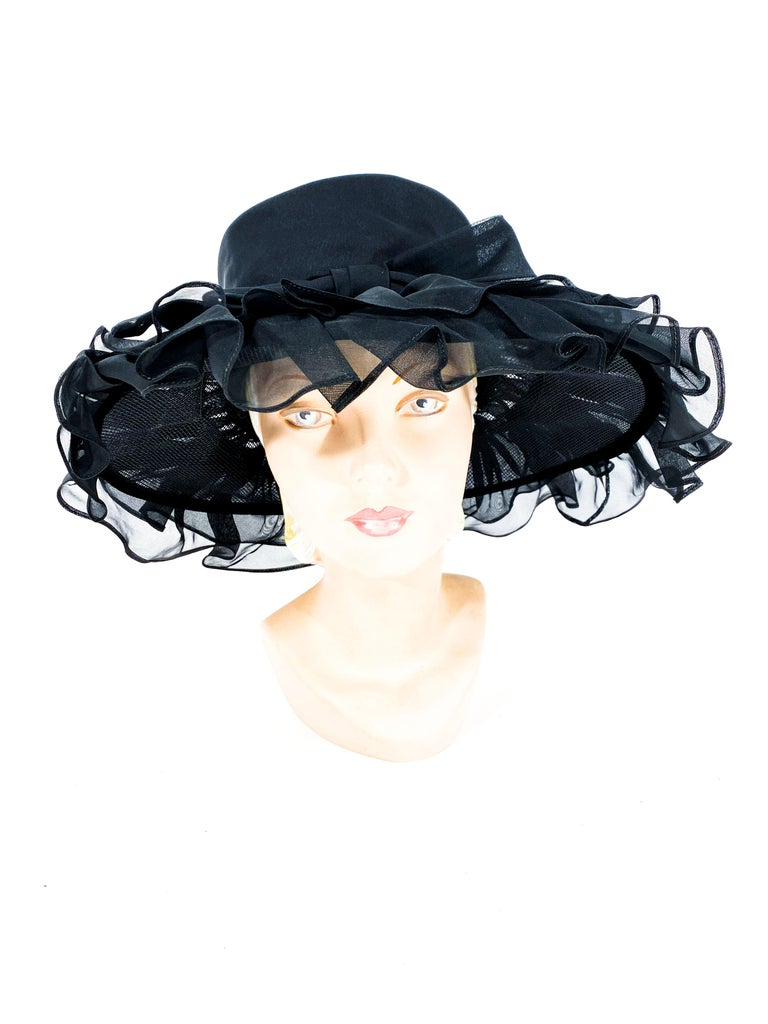 Late 1960s to early 1970s black wide brimmed hat decorated with a double row of organza ruffles, a tall crown, and an oversized bow centered on the band.