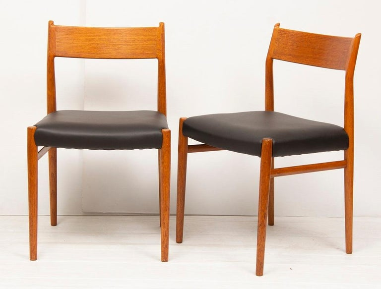 An original Danish 1960s set of four Arne Vodder for Sibast Scandinavian furniture teak dining chairs. Model number 418. Reupholstered in black leather. In very good vintage condition. On display at The Old Cinema in Chiswick.  Dimensions: Depth