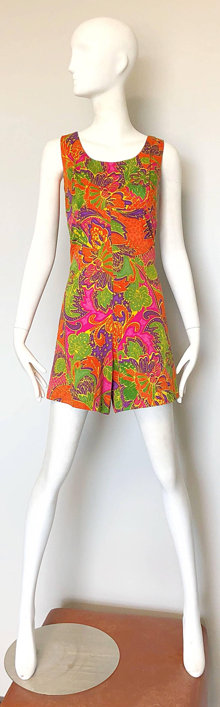Rare 1960s ALFRED SHAHEEN colorful tropical jumpsuit romper! Features colorful tropical Hawaiian prints throughout. Vibrant colors of orange, purple, hot pink, yellow and green throughout. Full metal zipper up the back with hook-and-eye closure.