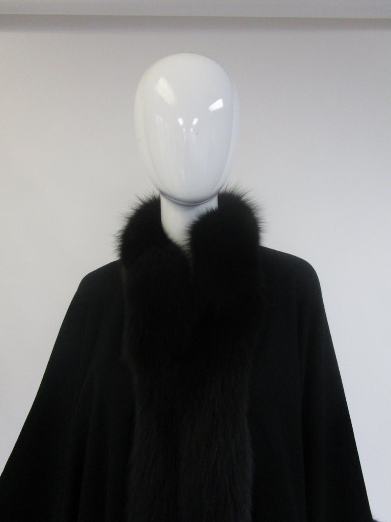 Wrap up in this incredibly warm and striking cape from Alixandre! It consists of a wool blend felt body with undulating black fox fur trim. The way it drapes over the wearer almost gives the appearance of sleeves. The back of the cape drapes