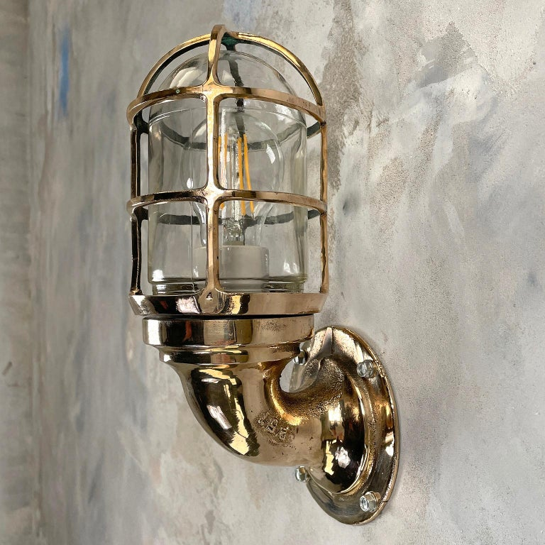 A vintage industrial 1960s Pauluhn bronze 90 degree wall sconce with industrial style cage & glass dome. Manufactured by American Company, Crouse-Hinds. Reclaimed and professionally restored by hand in UK by Loomlight, ready for contemporary