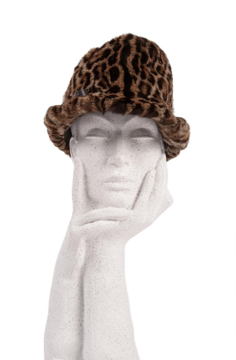 This is a 1960s sublime animal print fur hat in the style of Elizabeth Taylor.  The design is made from soft genuine fur showcasing the characteristic black ocelot spots on a beige to caramel background.   The hat features a high crown with a