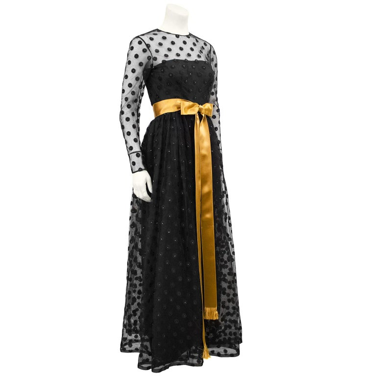 Gorgeous black long sleeve gown from the 1960s. The label is from Stanley Korshak, a famous upscale ladies boutique in Dallas whose heigh day was from the 1930s to the 1980s. The strapless tea length ballgown has a long sleeve black net overlay that