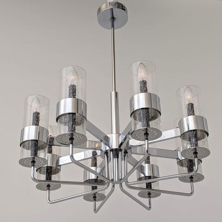 Unique Arredoluce style model blending a Classic chandelier structure with a Minimalist modern bold approach, circa 1960s  8-arm deep chromed brass structure with thick mouth blowed glass hurricane full of little stretched air bubble.  Solid