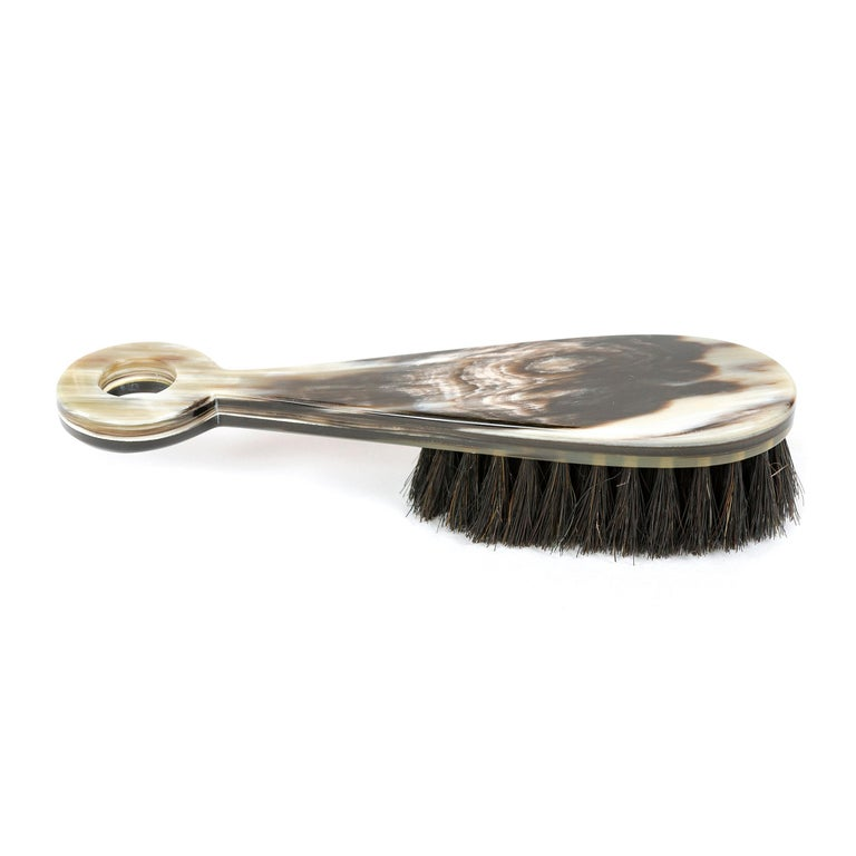 An elegant brush hand carved from cow horn with naturally occurring variations in color and pattern.