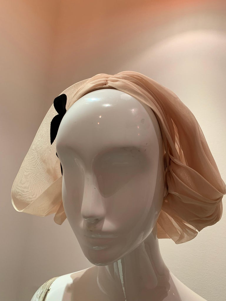 A wonderful 1960s Sonni hat:  A charmingly avant garde pleated ecru or blonde silk organza kerchief-style hat. Similar in silhouette to a bobbed hairstyle, it also evokes a romantic and historic Dutch look with a modern feel. Unusual and rare.