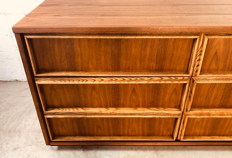 Vintage 1960s Bassett Furniture walnut and ash wood low dresser with 6-drawers. The ashwood accents all 6-drawers and the dresser floats on a black painted base. Newly refinished and in excellent condition. Marked in the drawer.