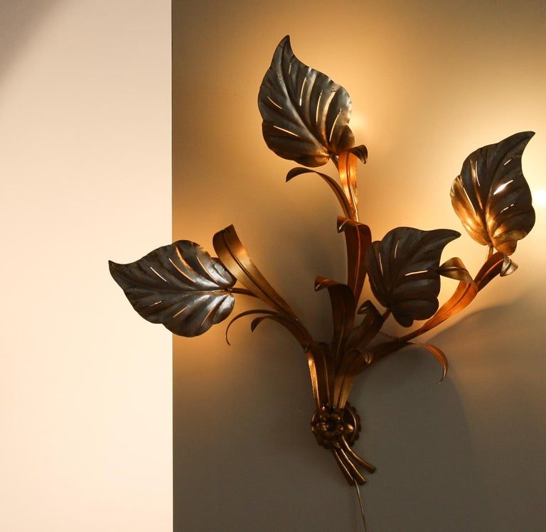 A nice large Italian wall lamp. This lamp has four large leaves behind it a light bulb which gives a beautiful shining. The lamp is made of metal and painted with a gold and ivory, silver lacquer. Period 1970s. Dimensions: H 90 cm, W 100 cm, D