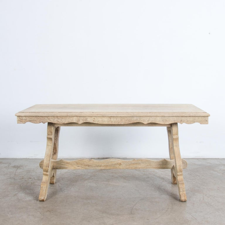 A typical mid-20th century Belgian style re-imagines traditional shapes in thick slabs of oak. Rustic simplified, with an elegant note of classical style. Thick legs support the tabletop from either side, supported by a trestle post. With clear oil