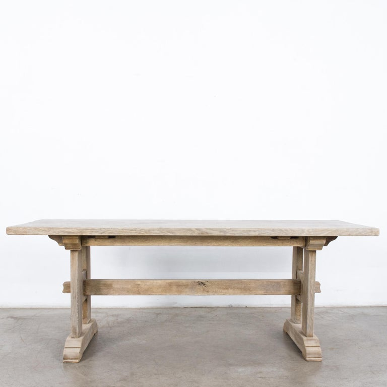 A bleached oak dining table from France, circa 1960. A sturdy tabletop sits atop trestle legs. An intricate arrangement of pegs and slats provides decorative support. The oak has been restored to a bright bleached finish. An elegant construction