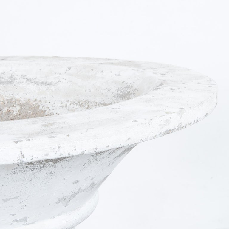 This trumpet-shaped concrete planter with a solid, circular foot was made in Belgium, circa 1960. Ribs encircling the body accentuate its pleasing curve. The distressed, white patina lends a rustic touch to the planter's understated elegance.