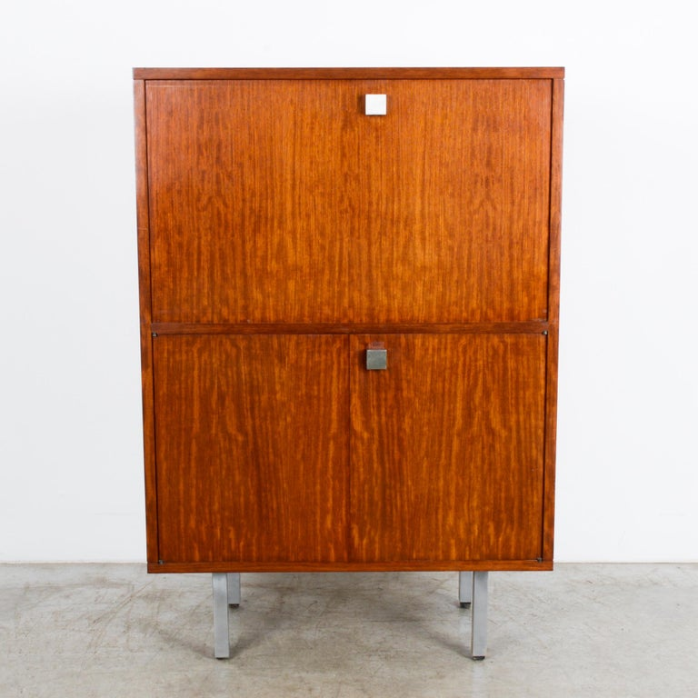 A teak cabinet from Belgium, circa 1960, from the studio of furniture designer Alfred Hendrickx. A cubic cabinet raised on simple silver legs, cleverly stores a concealed secretary desk. An upper door folds down to reveal a writing desk, complete