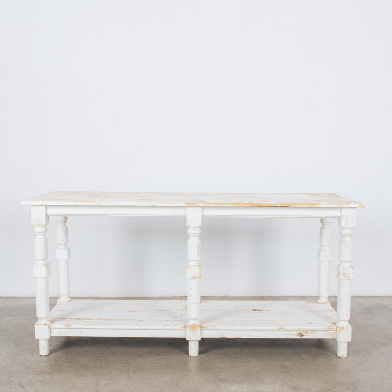 A wooden drapers table from Belgium, circa 1960. Six turned legs support a square tabletop; below, a lower platform serves as storage space. The table is painted a crisp, cheerful white. The paint has worn away along the lines of the grain to create